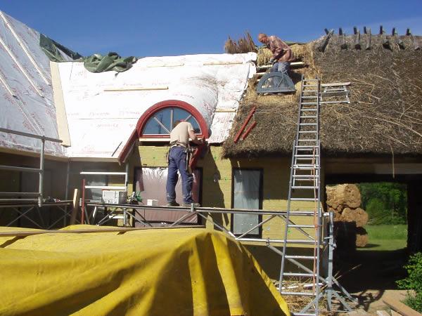 Bilden visar till höger ett traditionellt vasstak på läkt och till vänster ett tillbygge med råspont och tyvekduk.